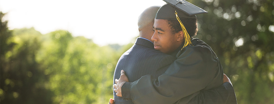 Picture of a high school male dressed in a graduation gown hugging his father.
