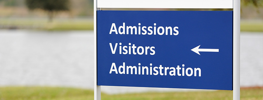 Picture of a sign that reads admissions, visitors, and administration