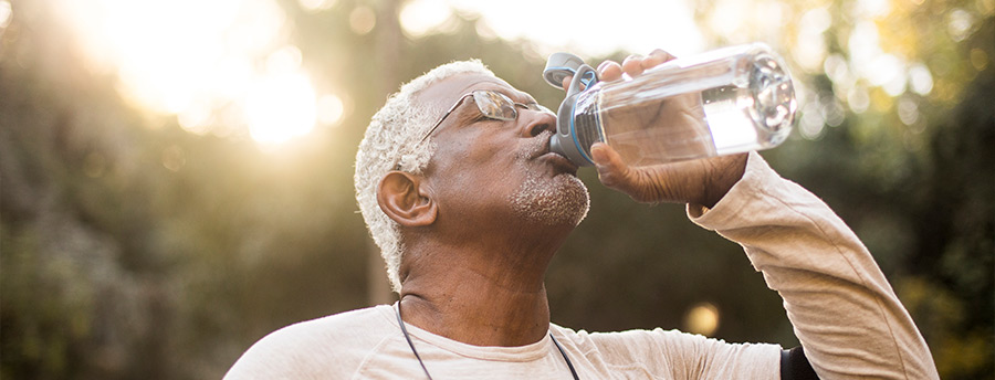 A man drinking out of a water bottle after exercising.
